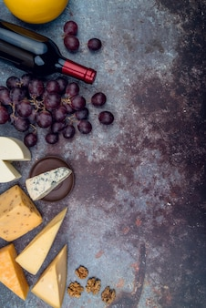 Vista superior deliciosa selección de quesos con vino y uvas