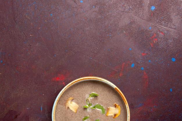 Vista superior deliciosa sopa de champiñones dentro de la placa en el espacio oscuro