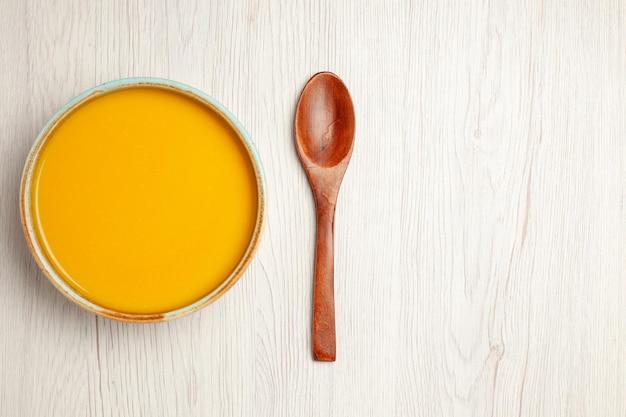 Vista superior deliciosa sopa de crema sopa de color amarillo en el plato de cena de crema de comida de salsa de sopa de escritorio de madera blanca