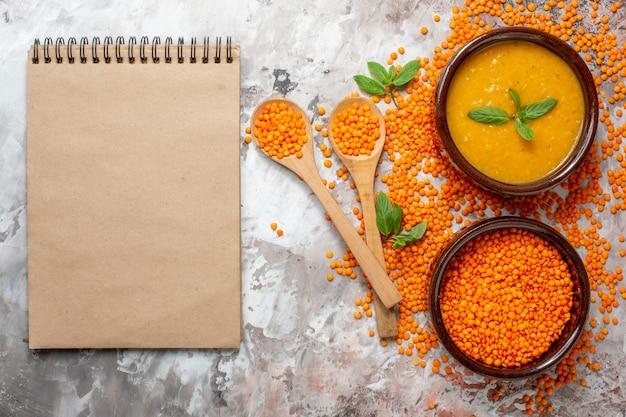 Vista superior deliciosa sopa de lentejas con lentejas crudas en una superficie liviana sopa de plantas color comida semilla plato