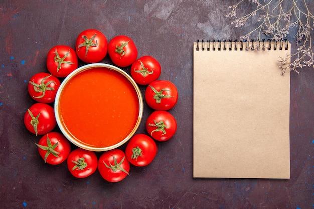 Vista superior deliciosa sopa de tomate con tomates rojos frescos en el plato de cena de comida de sopa de tomate de fondo oscuro