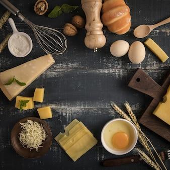 Vista superior de una deliciosa tabla de quesos con nueces, huevos y harina en una mesa con espacio de copia