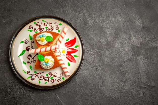 Vista superior de la deliciosa tarta de crema dulce porciones de pastel dentro de la placa diseñada sobre fondo oscuro pastel de color crema de galleta dulce