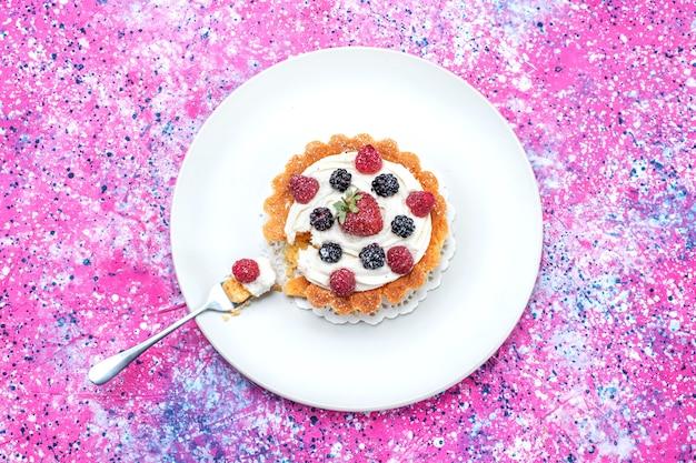 Vista superior de una deliciosa tarta cremosa con diferentes bayas frescas dentro de la placa en brillante, baya fresca agria