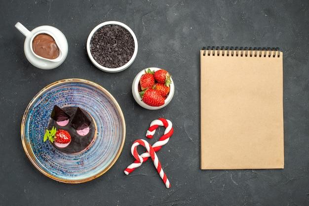 Vista superior deliciosa tarta de queso con fresa y chocolate en cuencos de placa ovalada con fresas dulces de navidad de chocolate un cuaderno sobre fondo oscuro aislado