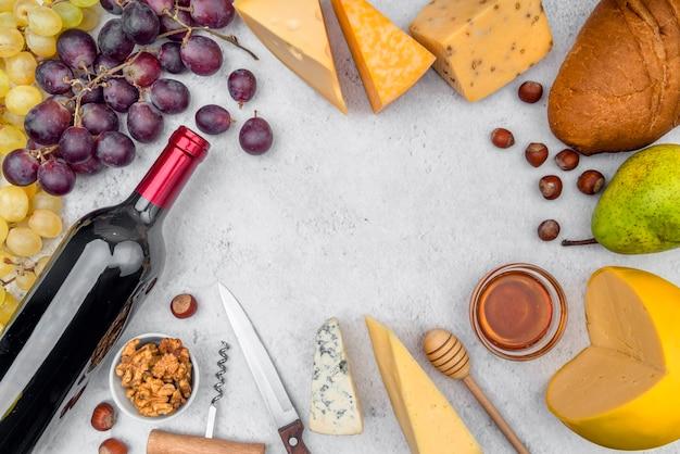 Vista superior deliciosa variedad de queso con botella de vino