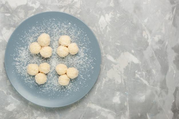Vista superior de deliciosas bolas dulces de caramelos de coco sobre superficie blanca