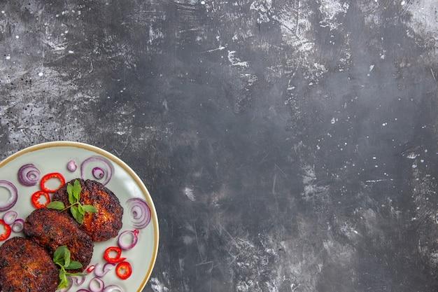 Vista superior deliciosas chuletas de carne con aros de cebolla