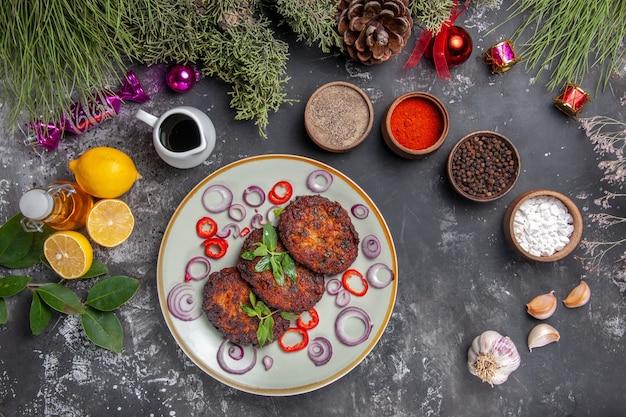Vista superior deliciosas chuletas de carne con condimentos en un plato de fotos de comida de escritorio gris claro