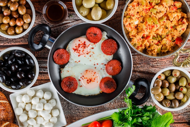 Vista superior deliciosas comidas en una olla y sartén con encurtidos en tazones sobre superficie de madera