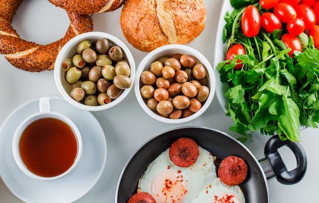 Vista superior deliciosas comidas en una olla con una taza de té, panecillos turcos, tomates, verduras en la superficie blanca