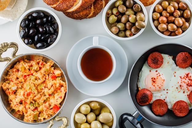 Vista superior deliciosas comidas en sartén y olla con pepinillos, una taza de té en la superficie blanca