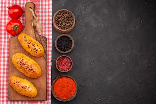 Vista superior deliciosas empanadas al horno con diferentes condimentos en el fondo oscuro pastelería hornear masa horno pastel pastel de carne