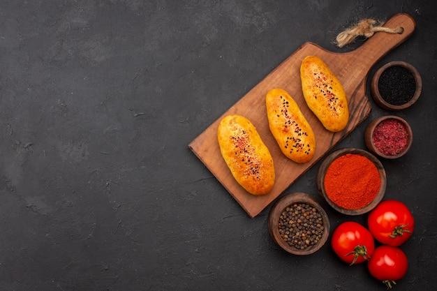 Vista superior deliciosas empanadas al horno recién salido del horno con condimentos en el fondo gris horno de pastel de carne pastelería pastel hornear