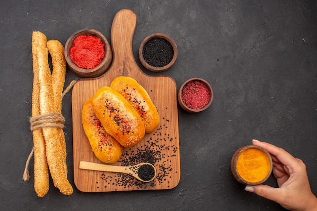 Vista superior deliciosas empanadas horneadas recién salidas del horno con diferentes condimentos en el escritorio gris horno de pastel de carne pastel de pastelería hornear