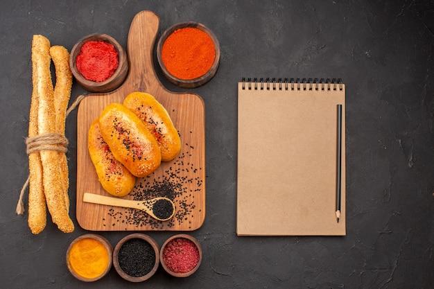 Vista superior deliciosas empanadas horneadas recién salidas del horno con diferentes condimentos en el fondo gris horno de pastel de carne pastel de pastelería hornear