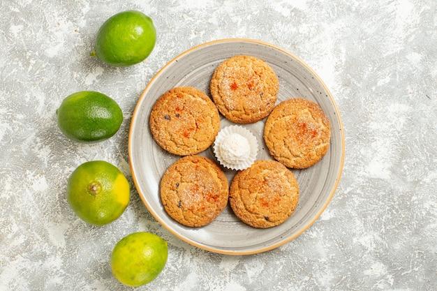Vista superior deliciosas galletas de arena con limones verdes sobre fondo blanco.