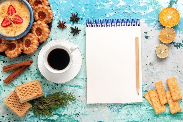 Vista superior deliciosas galletas de azúcar con gofres, café y postre de fresa en la superficie azul