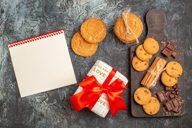 Vista superior de deliciosas galletas, barras de chocolate y caja de regalo, cuaderno de espiral sobre una superficie oscura helada