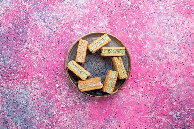 Vista superior de deliciosas galletas de gofres dentro de la placa en la superficie rosa