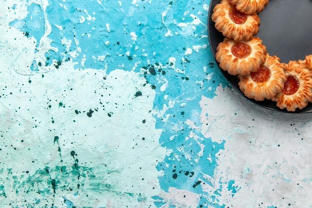 Vista superior deliciosas galletas redondas formadas con mermelada dentro de la placa negra sobre el fondo azul claro pastel de galleta dulce de azúcar de galleta
