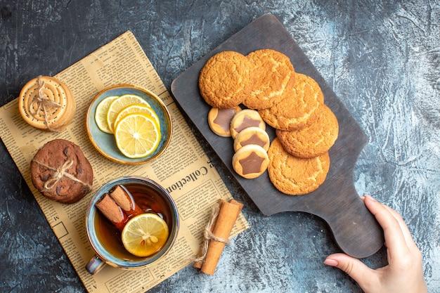 Vista superior de deliciosas galletas y una taza de té negro con limón canela en un periódico viejo