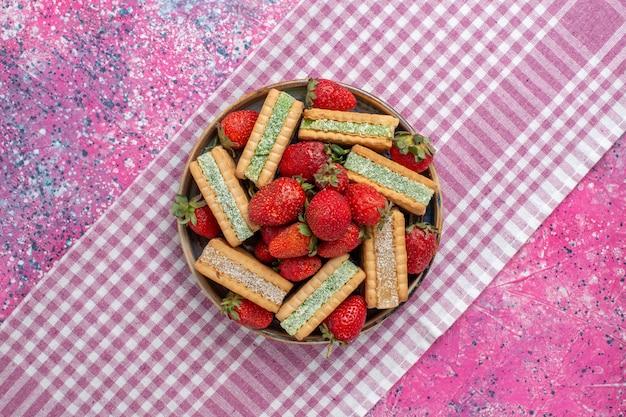 Vista superior de deliciosas galletas waffle con fresas rojas frescas en la superficie rosa
