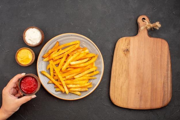 Vista superior deliciosas papas fritas con condimentos en el fondo oscuro comida de papa hamburguesa de plato de comida rápida