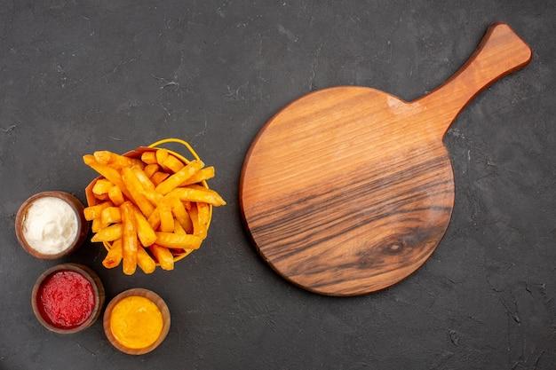 Vista superior deliciosas papas fritas con condimentos en el fondo oscuro, comida rápida, plato de papa, hamburguesa, comida