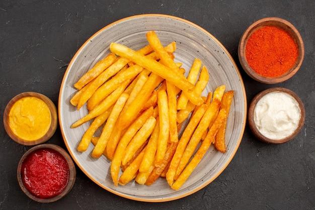 Vista superior deliciosas papas fritas con condimentos en el fondo oscuro plato comida de papa hamburguesa de comida rápida