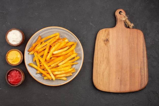 Vista superior deliciosas papas fritas con condimentos en el plato de comida rápida de hamburguesa de comida de patata de fondo oscuro