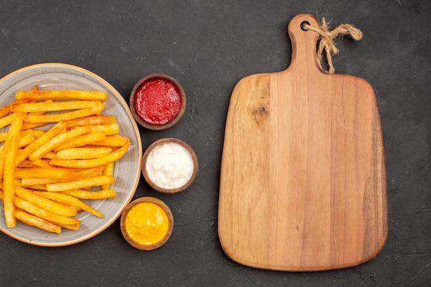 Vista superior deliciosas papas fritas con condimentos sobre fondo oscuro plato de comida de hamburguesa de comida rápida de papa