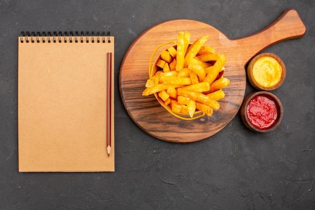 Vista superior deliciosas papas fritas dentro de la canasta con salsas en el fondo oscuro merienda hamburguesa comida rápida comida de papa