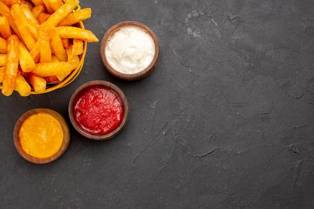 Vista superior deliciosas papas fritas con salsa de tomate, mostaza y mayyonaise sobre fondo oscuro hamburguesa comida rápida plato de papa