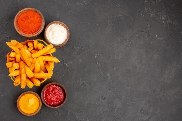 Vista superior deliciosas papas fritas con salsas en el fondo oscuro plato hamburguesa comida rápida papa comida