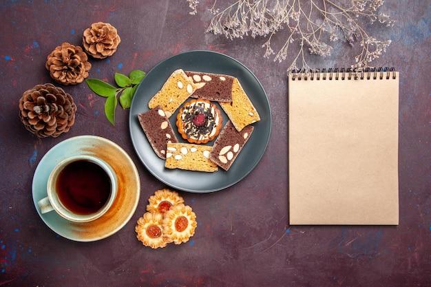 Vista superior de deliciosas rebanadas de pastel con galletas y una taza de té sobre un fondo oscuro, galleta, galleta, pastel, té, postre dulce