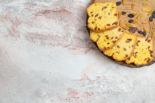Vista superior de deliciosas rebanadas de pastel con pasas en el escritorio blanco