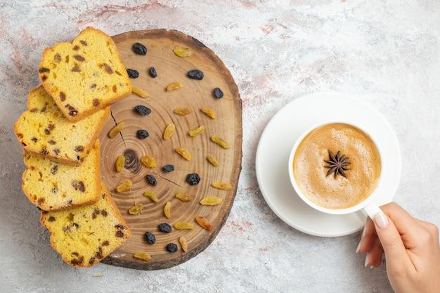 Vista superior de deliciosas rebanadas de pastel con pasas y una taza de café sobre el fondo blanco.