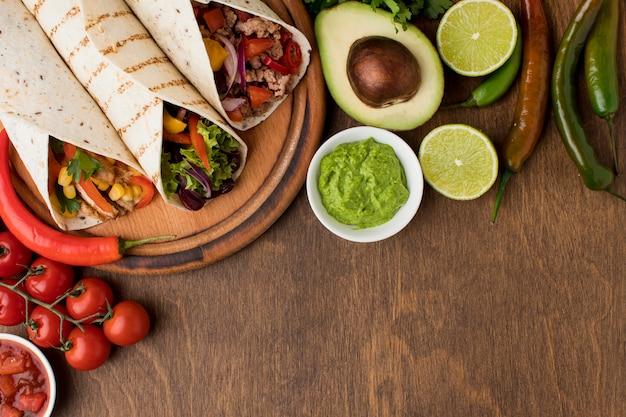 Vista superior deliciosas tortillas con guacamole sobre la mesa