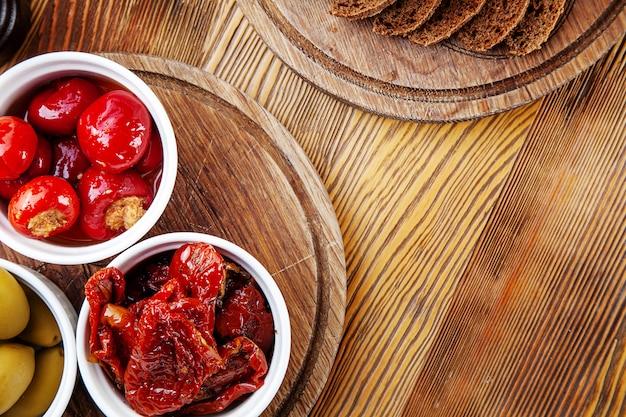 Vista superior con delicioso aperitivo italiano. tomates secados al sol, aceitunas y pimientos rellenos en especias italianas en una composición con pan diferente sobre fondo de madera. copia espacio comida plana