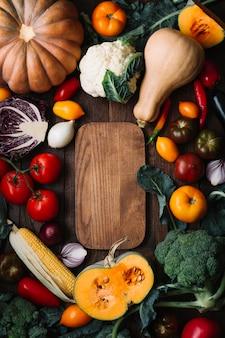 Vista superior delicioso arreglo de verduras con tabla de cortar