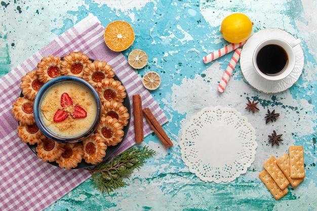 Vista superior del delicioso azúcar con taza de café y postre de fresa en superficie azul