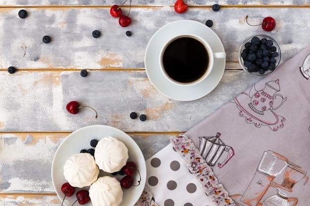 Vista superior de un delicioso desayuno con cruasanes, café y arándanos y cerezas sobre la mesa