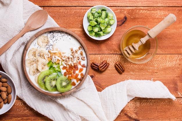 Vista superior delicioso desayuno tazón con kiwi y yogurt