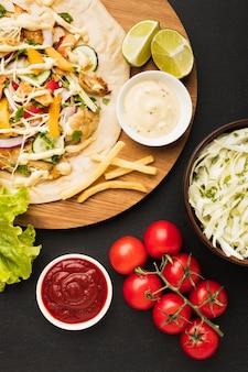 Vista superior del delicioso kebab con tomates y limas