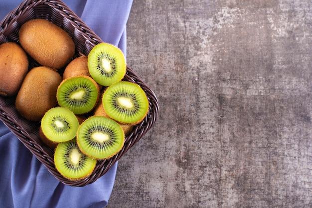 Vista superior delicioso kiwi fresco en canasta con espacio de copia en tela morada