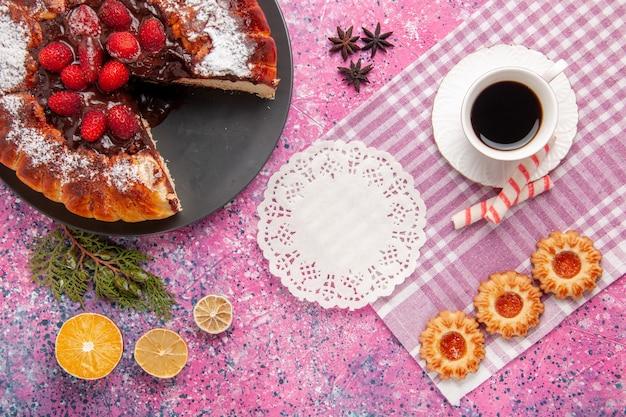 Vista superior delicioso pastel de chocolate con galletas y una taza de té sobre fondo rosa pastel de postre de azúcar dulce galleta hornear pastel