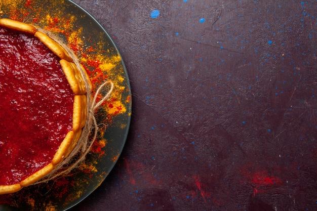 Vista superior delicioso pastel con crema roja y galletas sobre fondo oscuro pastel de galletas pastel de postre de azúcar galleta dulce