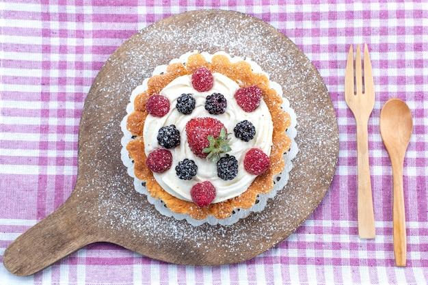 Vista superior del delicioso pastel cremoso con bayas frescas en luz brillante, frutas frescas agrias