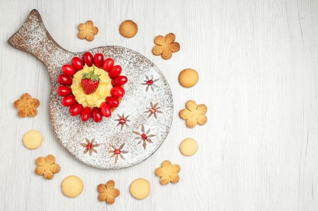 Vista superior delicioso pastel cremoso con cornejos y galletas en el escritorio blanco